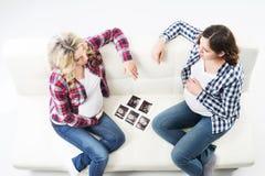 观看超声波照片的两名可爱的孕妇 免版税库存图片