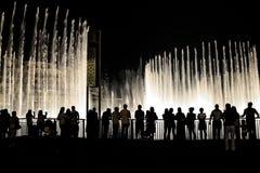 观看迪拜喷泉的人们在晚上 库存照片