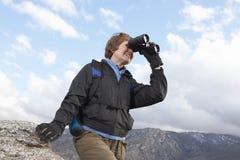 观看通过双筒望远镜的女性远足者 图库摄影