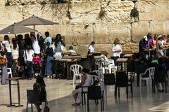 观看通过篱芭的未认出的犹太人妇女对品行成人仪式仪式的女性区段在西部墙壁附近 免版税图库摄影
