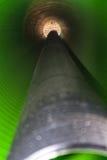 观看长的塑料管的里面在地面下 免版税图库摄影
