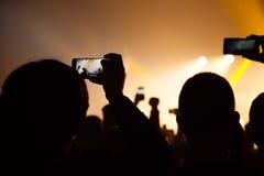 观看音乐会和某人的人们射击照片和录影有手机的 库存照片