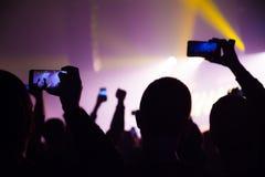 观看音乐会和某人的人们射击照片和录影有手机的 库存图片