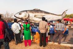 观看鲨鱼的雕塑在普遍的春天果阿狂欢节的一个移动的平台的人们 库存图片