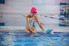 观看更加年轻一个的更老的姐妹游泳沿水池引导 库存照片