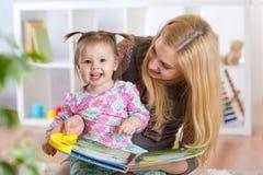 观看婴孩小册子的愉快的少妇和儿童女孩 免版税图库摄影