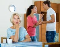 观看年轻家庭夫妇的成熟妇女在家争吵 免版税库存图片