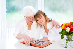观看黑白照片的妇女和她的母亲 免版税库存照片