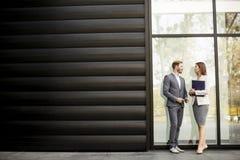 观看年轻的商人谈话和提供室外 免版税库存图片