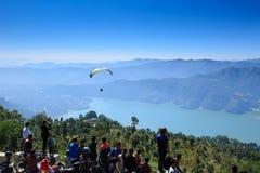 观看滑翔伞飞行的人们反对蓝天 免版税库存照片