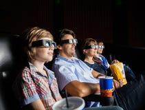观看3D电影的家庭在剧院 免版税库存照片