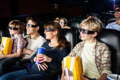 观看3D电影的微笑的家庭在剧院 免版税库存图片