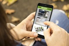 观看cctv app的妇女用电话在公园 免版税图库摄影