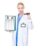 戴视力检查表和眼镜的眼镜师医生 免版税图库摄影