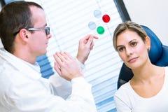 视力测定概念-相当安排的少妇她的眼睛被审查 免版税库存图片