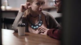 视图通过视窗 谈话有吸引力的年轻的夫妇坐在咖啡馆在晚上和,一起花费时间 股票录像
