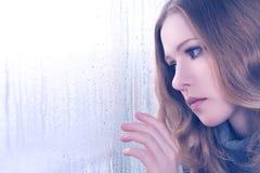 视窗的悲伤女孩在雨中 免版税库存照片