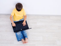 角度男孩高膝上型计算机一点使用 免版税库存图片
