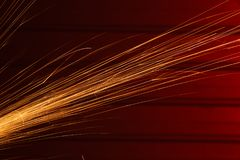 角度研磨机在红色背景发火花 免版税库存图片