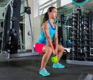 觚kettlebell蹲坐在健身房的妇女锻炼 免版税库存照片