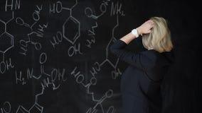 解决一个难题的妇女的画象,站立在有惯例的委员会附近 科学的概念 格式 影视素材
