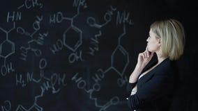 解决一个难题的妇女的画象,站立在有惯例的委员会附近 科学的概念 格式 股票视频