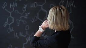 解决一个难题的妇女的画象,站立在有惯例的委员会附近 科学的概念 格式 股票录像