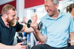 解决与个人教练员的老人在健身房 免版税库存照片