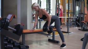 解决与哑铃重量的白肤金发的妇女在一间现代健身房用倾斜今后在长凳的各种各样的设备 股票视频