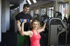 解决与在健身房的哑铃的健身夫妇 免版税库存照片