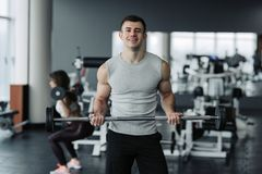 解决与在健身房的哑铃的英俊的肌肉人 免版税图库摄影