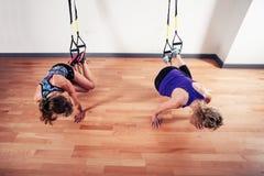 解决与在健身房的皮带的两名妇女 免版税库存照片