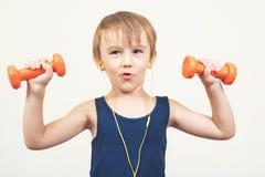 解决与在白色背景的哑铃的健康小男孩 健康生活方式、孩子体育和童年 前逗人喜爱的孩子男孩 图库摄影