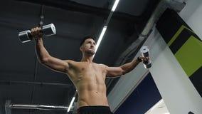 解决与抽的胳膊的哑铃的年轻体育人在健身房干涉 影视素材