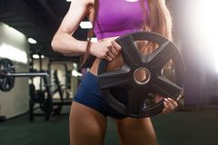 解决与杠铃的运动员妇女 比基尼泳装做在健身房的运动服的健身女孩锻炼 库存图片