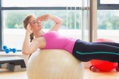 解决与锻炼球的适合的妇女在健身演播室 库存图片