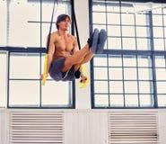 解决与trx健身s的赤裸上身的肌肉体操男性 库存照片