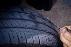 解决从钉子锐利螺丝的维护泄了气的轮胎问题 汽车 库存图片