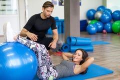 解决在与个人教练员的一间健身房的妇女 免版税库存照片