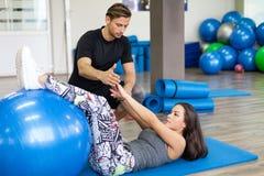 解决在与个人教练员的一间健身房的妇女 库存图片