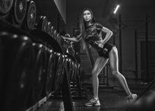 解决在健身房的年轻美丽的亚裔妇女画象  免版税库存图片