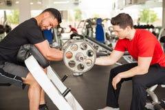 解决在健身房的男性朋友 免版税库存图片