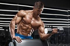 解决在健身房的肌肉人做与杠铃的锻炼二头肌的,强的男性赤裸躯干吸收 库存照片