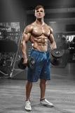 解决在健身房的肌肉人做与杠铃,强的男性赤裸躯干吸收的锻炼 免版税库存照片