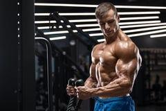 解决在健身房的肌肉人做二头肌的,强的男性赤裸躯干吸收exercisesl 免版税库存图片