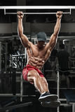 解决在健身房的肌肉人,做在一架单杠的胃锻炼,强的男性赤裸躯干吸收 免版税图库摄影