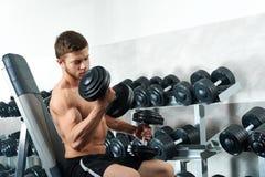解决在健身房的英俊的年轻运动员 库存照片