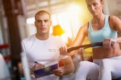 解决在健身房的锻炼机器的妇女和教练员 图库摄影