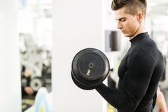 解决在健身房的年轻英俊的人 库存照片