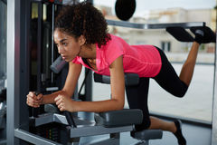 解决在健身房的年轻运动女孩做屁股和腿的锻炼 库存照片